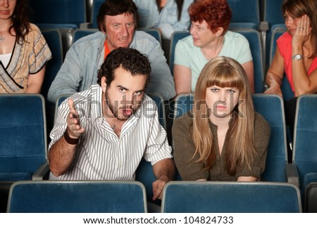 Serious movie fans angry in a theater
