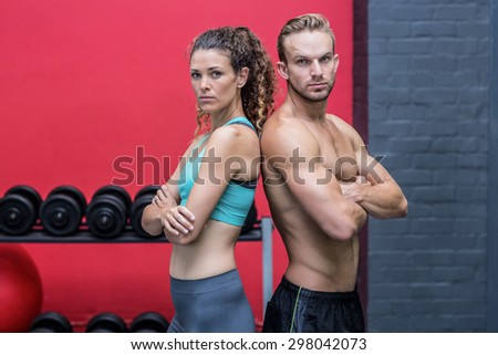 Serious muscular couple giving back to back