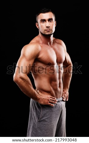Serious muscular sportsman over black background - stock photo