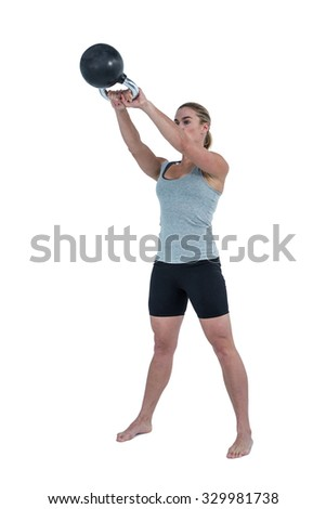 Serious muscular woman lifting kettlebell on white background