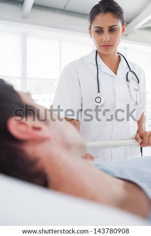 Serious nurse taking care of a lying patient in his bed - stock photo