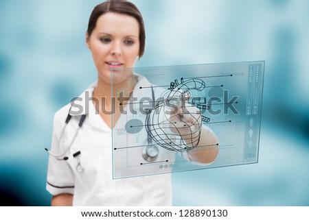 Serious nurse using a futuristic interface - stock photo
