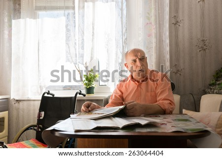Serious Old Bald Man in Orange Shirt Sitting at his Table with Newspaper While Looking at Right Frame. - stock photo
