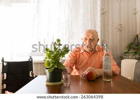 Serious Old Bald Man Sitting at the Table with Wine Bottle, Red Apple and Small Green Plant - stock photo
