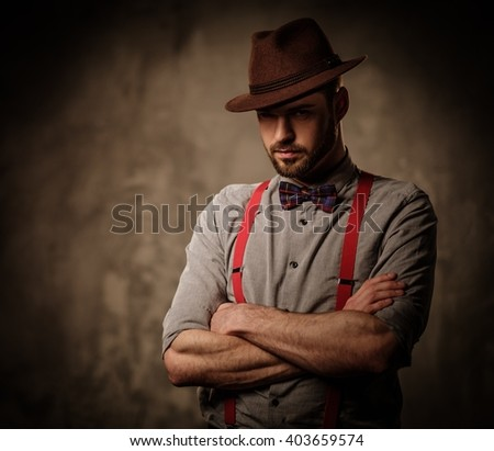 Serious old-fashioned man with hat wearing suspenders and bow tie, posing on dark background.