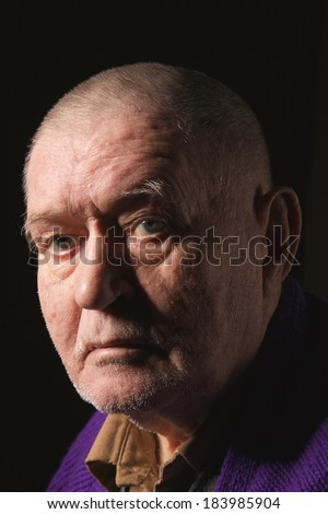 serious old man senior on black background looking at camera - stock photo