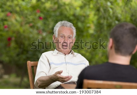 Serious old man talking with grandson and explaining by hand - stock photo