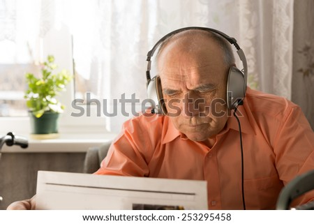 Serious Old Man with Headset Device Reading Newspaper Inside his Home. - stock photo