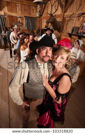 Serious old western couple in crowded saloon