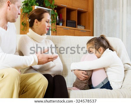serious parents scolding daughter in home interior