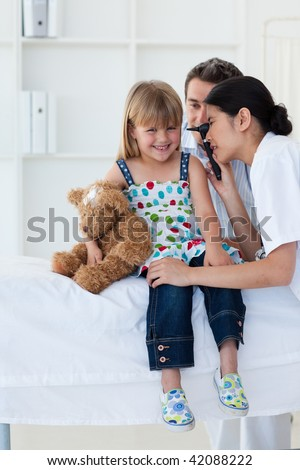 Serious patient examing littl girl's ears during a visit - stock photo