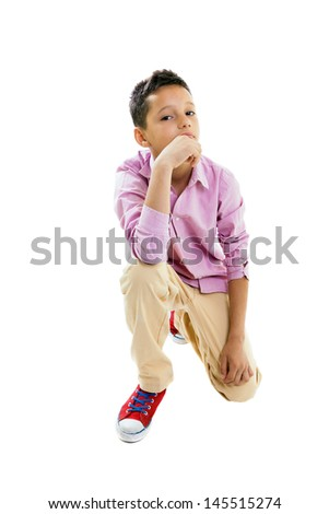 Serious, pensive young boy portrait leaning on his knee, holding his chin with right hand, close-up, full lenght body, isolated on white. - stock photo