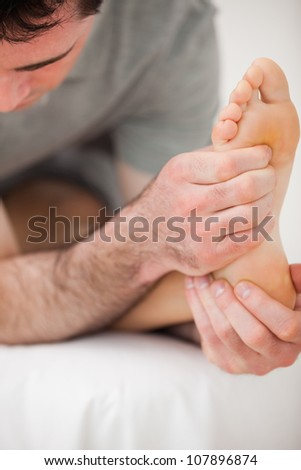 Serious physiotherapist making a joint mobilisation indoors - stock photo