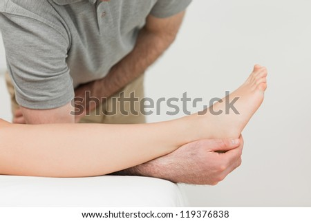Serious physiotherapist working on an ankle in a room - stock photo
