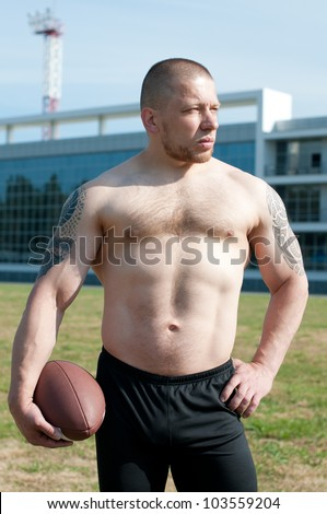 Serious player holding an american football - stock photo