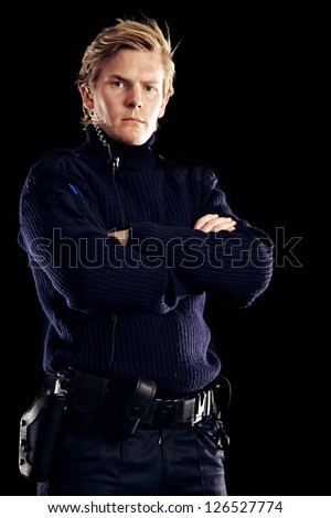 Serious police officer against black background ensuring we are safe from criminals - stock photo