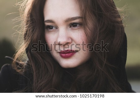 Serious portrait of beautiful woman outdoor, soft sunlight on her hair.