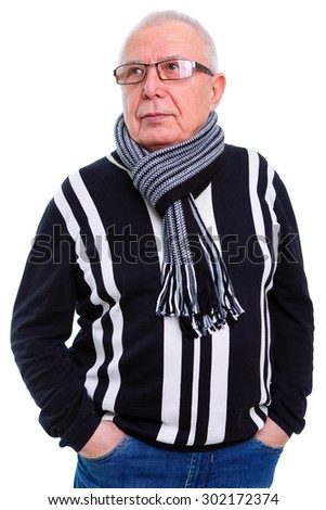 Serious portrait of old senior business man with glasses, dressed in sweater, jeans and scarf on the neck, looking to left, Isolated on white background - stock photo