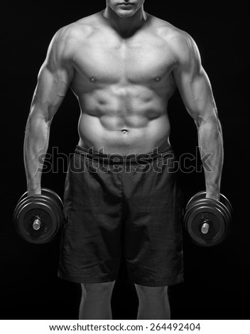 Serious powerful black and white muscular body of young sportsman standing shirtless with black dumbbells in hands, with swollen blood veins, isolated on black background. Dressed in black shorts - stock photo