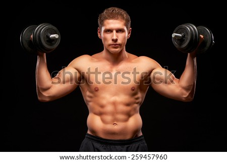 Serious powerful shirtless muscular sportsman pumping biceps muscles with black dumbbells, dressed in black shorts, looking at camera, isolated on black background - stock photo