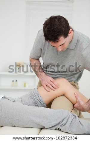 Serious practitioner holding the knee of a patient in a medical room - stock photo