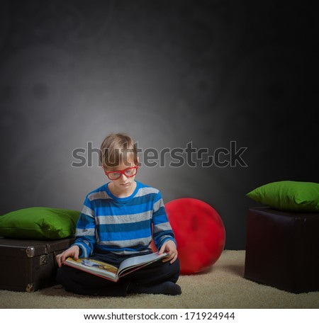 Serious preteen boy sitting on the floor and reading a book, dark background - stock photo