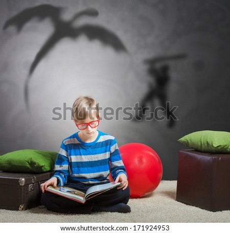 Serious preteen boy sitting on the floor and reading a story about a knight and a dragon