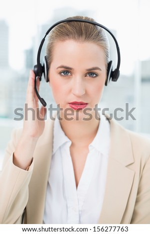 Serious pretty call center agent in bright office wearing headset