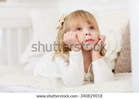 Serious pretty little girl lies on a sofa in the room and looks upwards. - stock photo