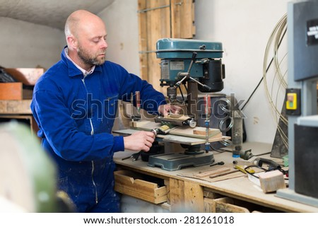 Serious professional woodworker working on a machine at wood workshop