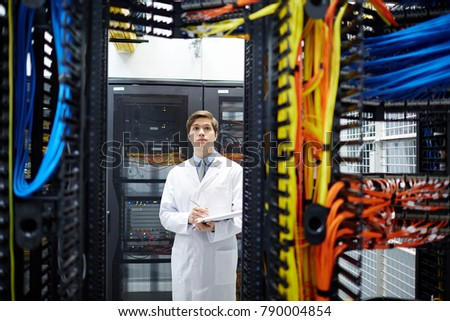 Serious programmer in whitecoat carrying out check-up of new hardware in mining farm