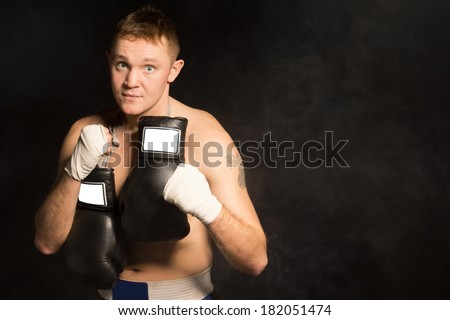 Serious resolute young boxer standing staring at the camera with his bandaged fists raised and his gloves slung around his neck, dark background with copyspace - stock photo