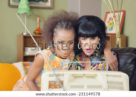 Serious retro 1960s friends watching television - stock photo