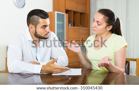 Serious russian couple with documents in apartment