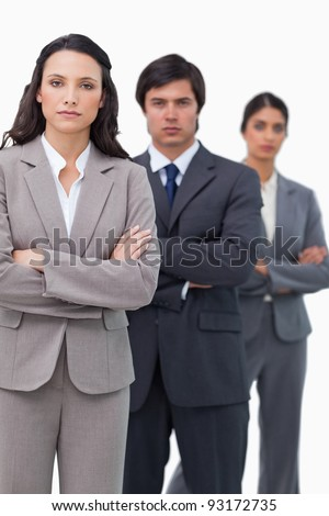 Serious salesteam standing together with folded arms against a white background