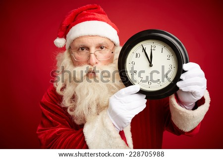 Serious Santa Claus holding clock with five minutes to midnight on - stock photo