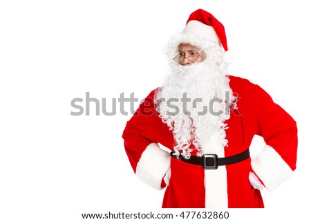 Serious Santa Claus looking away while standing on white background. Copy space.
