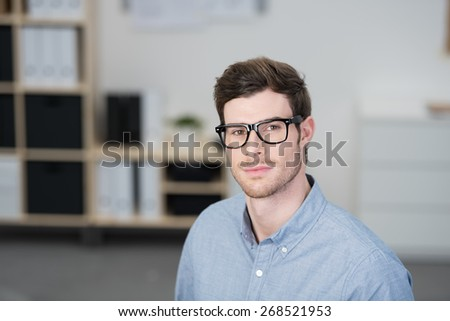 Serious scholarly young businessman wearing nerdy dark framed glasses looking directly at the camera, with copyspace
