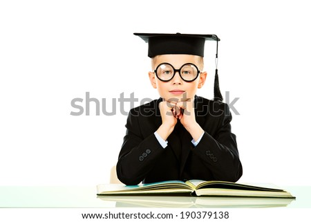 Serious schoolboy in academic hat sitting at the table with a book. Isolated over white. - stock photo
