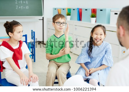 Serious schoolboy raising his hand to answer while one of his classmates laughing and the other one staying serious
