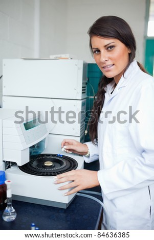 Serious scientist using a centrifuge in a laboratory - stock photo