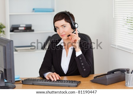 Serious secretary calling with a headset in her office