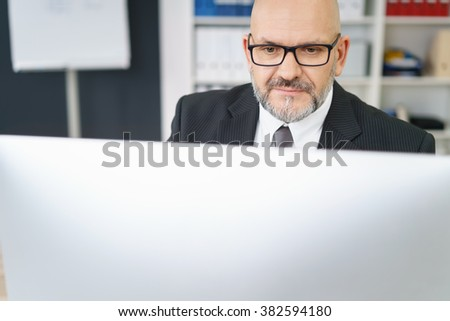 Serious senior business manager working at a desktop computer with a look of pensive concentration, view over the top of the monitor - stock photo