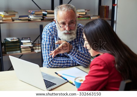 serious senior businessman explaining something to woman, looking at her and pointing at laptop. smiley young woman listening and looking at laptop in office - stock photo