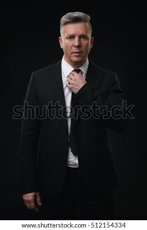 Serious senior businessman in black suit and white shirt.