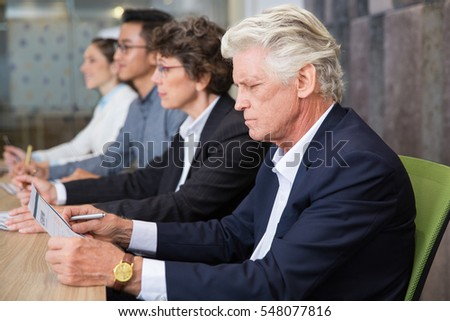 Serious senior businessman reading document
