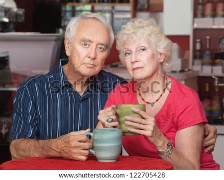 Serious senior couple at table in restaurant - stock photo