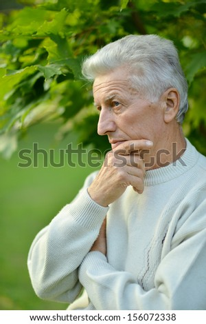 Serious senior man looking in park on green background
