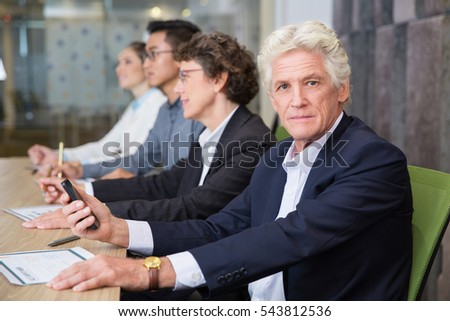 Serious senior man with phone at presentation