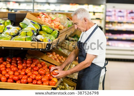 Serious senior worker taking tomato in supermarket